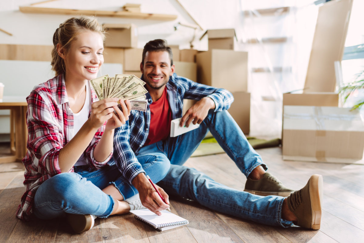 happy young couple with calculator and dollar bills after selling house for cash.