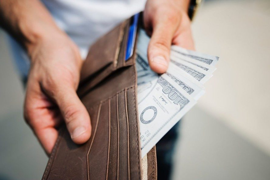 A man holding a brown wallet showing the cash he made from selling a house for cash.