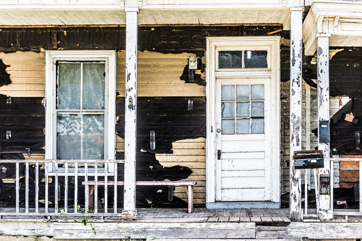 Old abandoned weathered wooden house with porch entrance, peeling paint, dirty windows