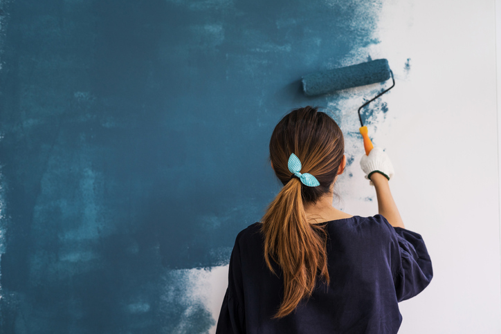 Woman painting a house to sell in Kansas City.