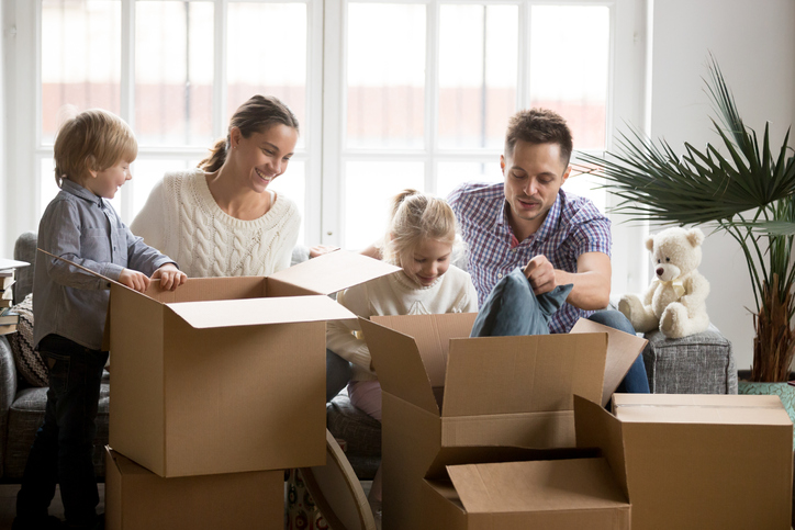 A family packing boxes and selling their house to cash buyers.