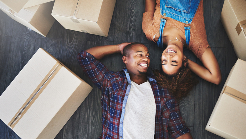 A young couple laying by moving boxes who is going to sell their house to cash buyers.