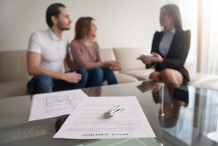 Young renters talking with someone about their rental agreement. We buy houses with tenants in Kansas City.